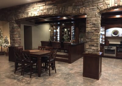This was a project that we framed as well as the cabinetry. We used Alder wood with a toffee color stain on the cabinets, wainscoting, column bases, and wood beams. The cabinets are lit in the back bar. There is crown moulding on both the bar and serving area. The elevated area at the bar is very special to the owners. They wanted lounge chairs instead of stools.